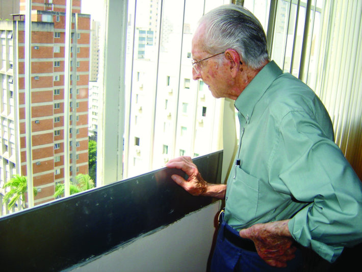 older man looks out of a window