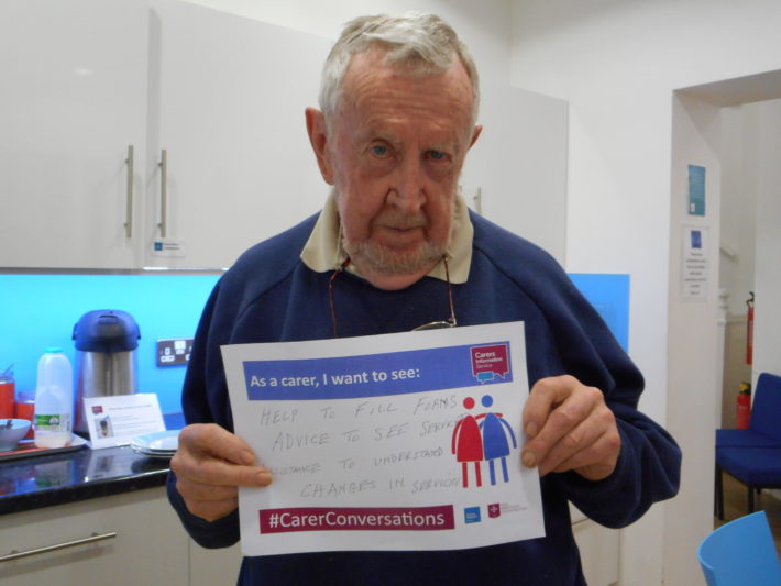 Carer holding pledge card