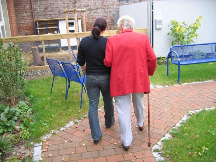 woman helping older woman with a stick take a walk in a garden