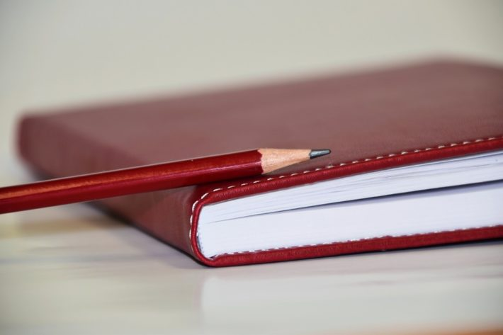 red notebook with pencil on top