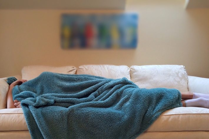 person on sofa lying down under a blanket